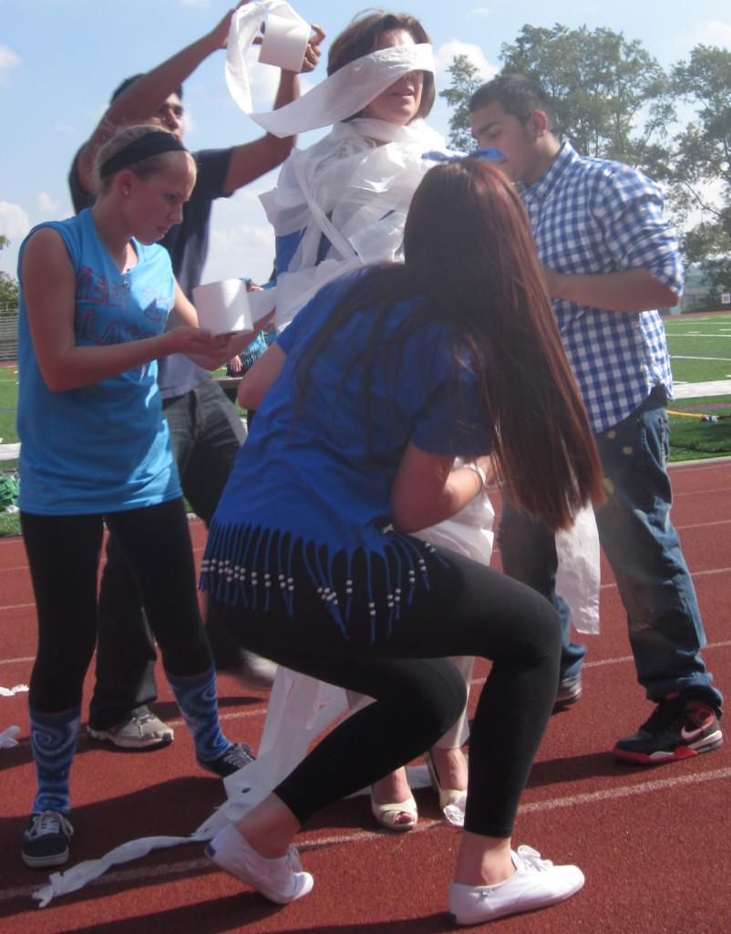 Sohpomores vigorously wrapping their teacher in toilet paper